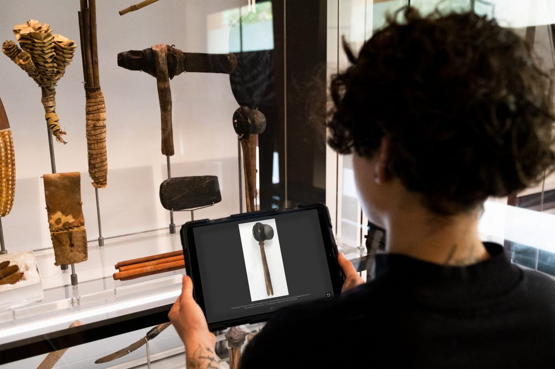 Elliotte holding iPad in front a collection of aboriginal artifacts.