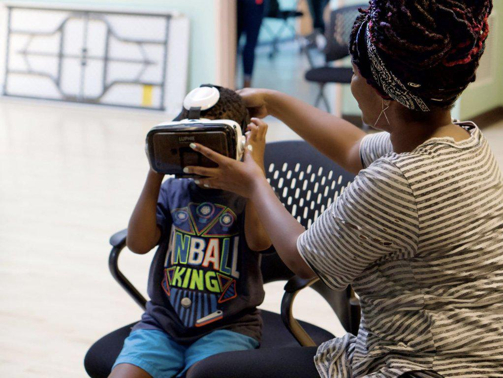 Little boy getting assisted with putting on a VR headset